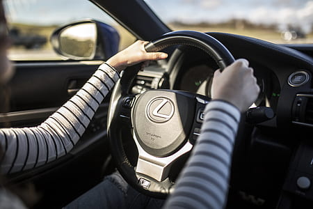 person holding on black Lexus car steering wheel