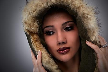 woman with full makeup wearing brown fur cap