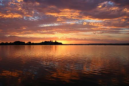 body of water under orange sunset