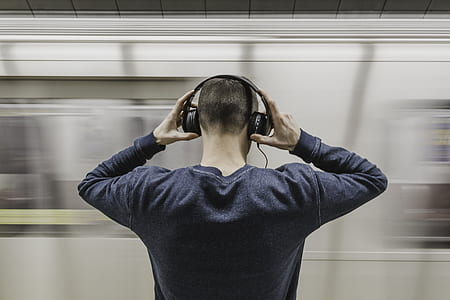 man wearing gray sweatshirt holding headphones in front on train station