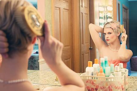 woman wearing pink towel grooms her hair
