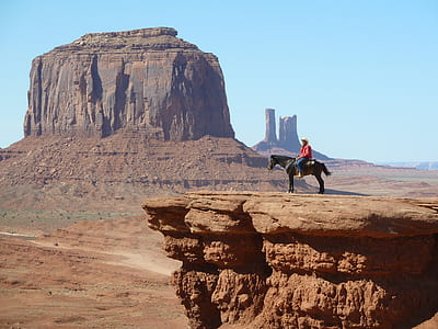 man riding on horse near rock cliff near canyon