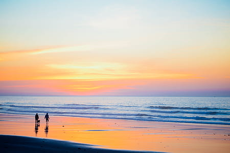 two persons standing at beach side during low tide and golden hour