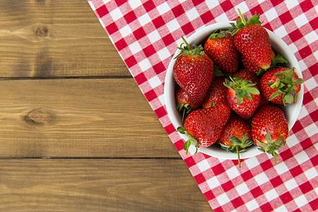 Bowl of strawberries on a wood table