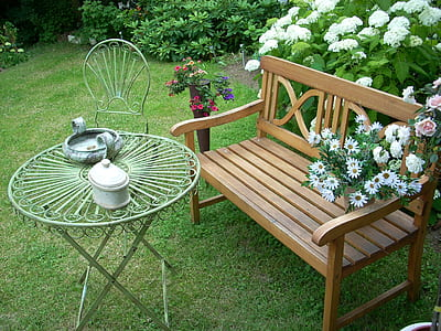 brown wooden bench and white metal patio set