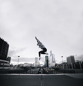 person wearing hoodie jumping on building photography