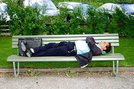 man in blue shirt and black pants sleeping on white wooden bench