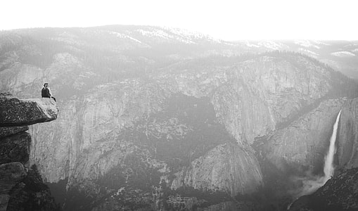 grayscale photo of person sitting on cliff