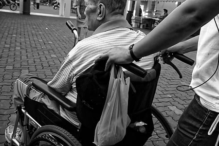 grayscale photo of man sitting in wheelchair