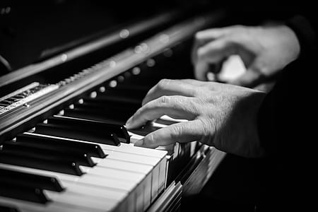 gray-scale photo of person playing a piano