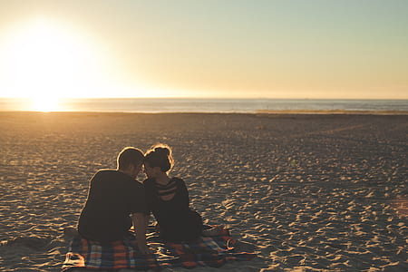 man and woman looking at each other on beach during sunset