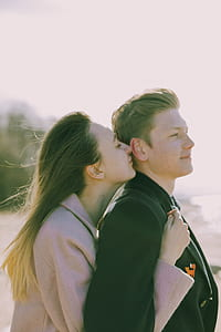 Woman Kissing the Back of Man's Ear Near Sea