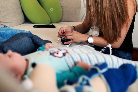 Woman Tieing Shoe Near Baby in Blue Stripe Onesie
