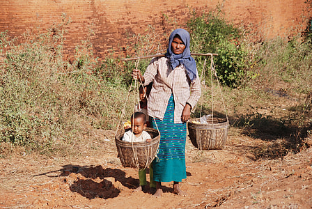 woman carrying basket with child during daytime