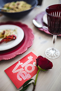 Fancy dinner with seafood pasta, crayfish and red wine by the table decorated with roses