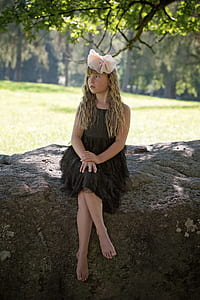 girl wearing black dress with pink bow accent headband sitting on grey rock under green leaf tree