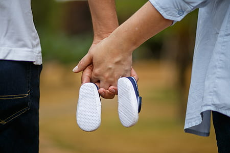 man and woman holding hands and holding pair of blue shoes