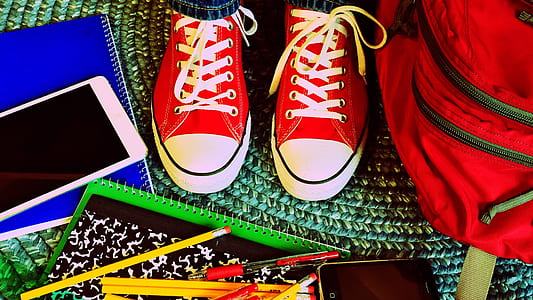 pair of red-and-white low-tops; books; pencils; smartphone; bag