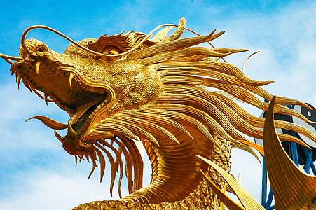 gold Chinese dragon monument during daytime