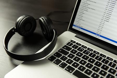 iTunes music app open on alaptop computer alongside headphones