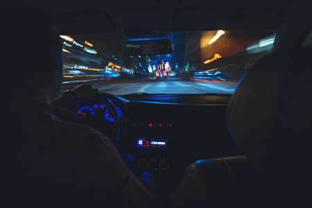 Man driving a car on the road at night