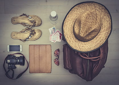 photography of brown hat on brown leather bag besides sunglasses, leather sandals, DSLR camera and silver iPhone 5s