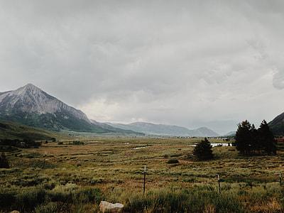 green grass lawn near mountain under white cloudy sky