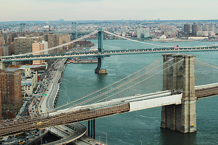 photo of gray concrete suspension bridges above body of water