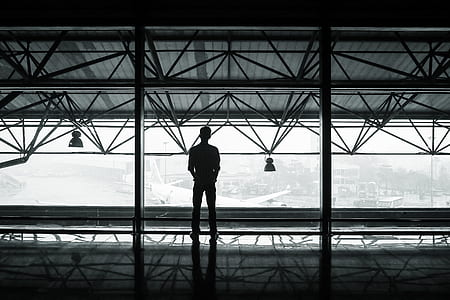 silhouette of man standing on glass window