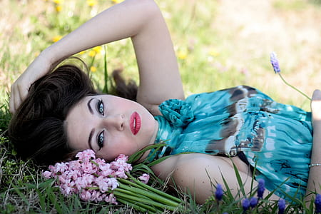 woman wearing blue sleeveless dress lying down on grass beside flowers