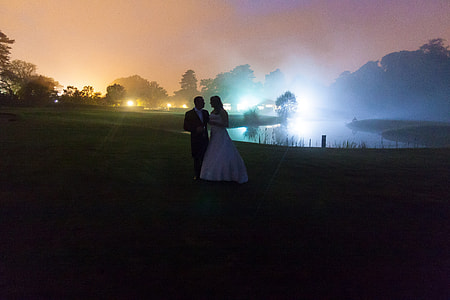bride and groom standing near lake