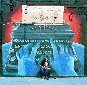 woman sitting on floor beside the typewriter graffiti