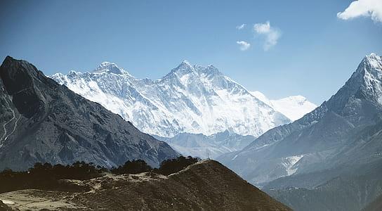 brown peak near white mountains at daytime