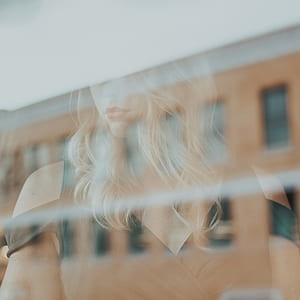 woman reflecting on clear glass window