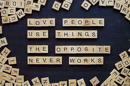 brown wooden scrabble chips forming love people use things the opposite never and works letters