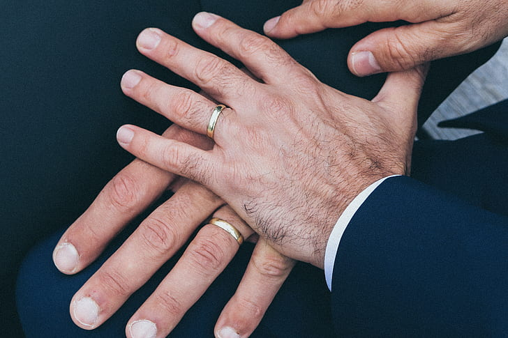 two persons wearing gold-colored rings