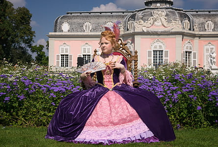 woman in pink and purple long-sleeved ball gown while holding hand fan