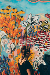 woman in black t-shirt looking at floral wall paintings during daytime