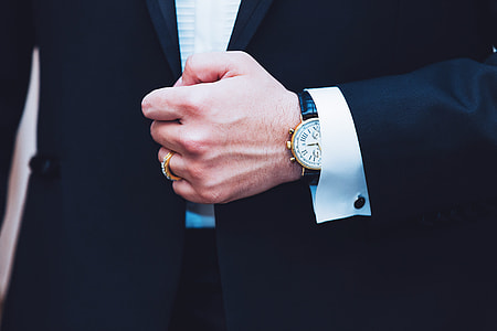 Business man wearing a suit showing hand and watch
