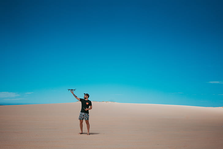 man wearing black t-shirt and gray shorts standing on dessert field landscape photography