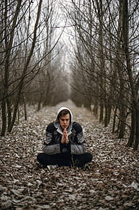 man wearing gray jacket and black pants meditating on road with dried leaves near trees