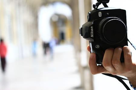 person holding black Nikon D70 in tilt shift lens photography