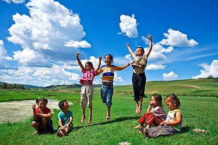 four children sitting on green grass and three children jumping taken under white clouds during daytime