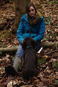 woman wearing windbreaker jacket facing the dog