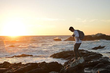 A man walking on a rocky coast