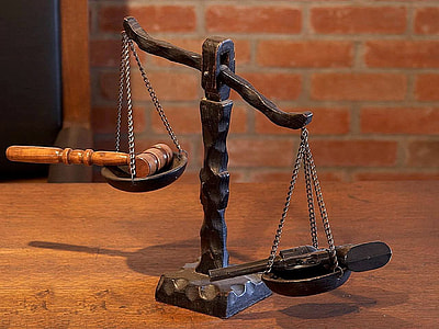 black balance scale with gavel and pistol