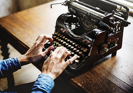 person's hands on top of typewriter