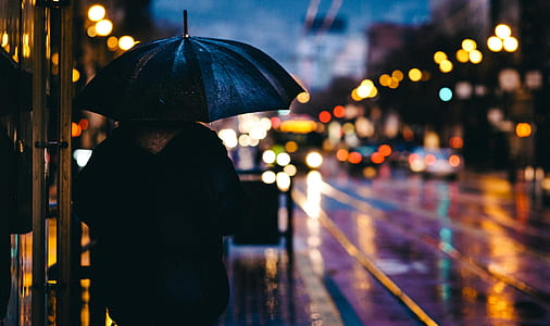 person holding black umbrella during night time
