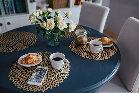 Round breakfast table with white flowers and golden coffee mats