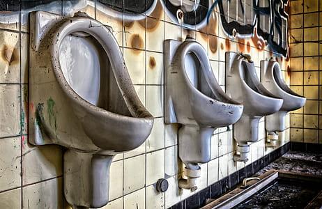 four gray ceramic urinals